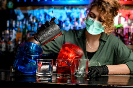 bartender girl in medical mask accurate pour drink from steel glass into glasses with ice. Blue and red warning lights inform about quarantine.