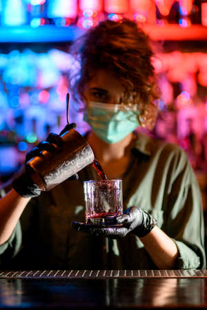 Woman barman in medical mask and black gloves holds glass and attentively pours drink into it.