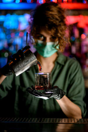 Woman barman in medical mask holds glass by one hand and energetically pours drink into it by other hand. Blue and red warning lights in background inform about coronavirus quarantine.
