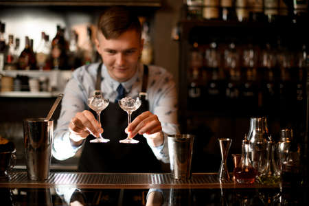 bartender holds in his hands two glasses with ice