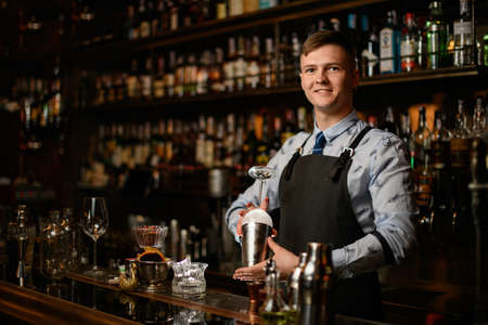 Professional young smiling barman preparing glass and shaker to make cocktail. Stock Photo