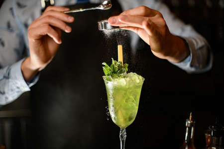 Close-up bartender decorates green alcoholic drink with ice in glass by powder. Stock Photo