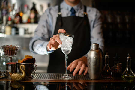 bartender holds transparent glass covered by sieve
