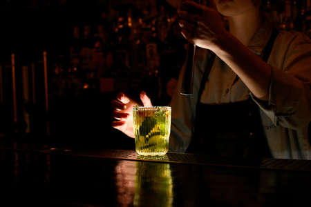 Fresh cocktail caipirinha stand on bar counter. Woman bartender behind bar holds steel madler in hand. Stockfoto