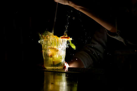 Close-up. Woman at dark bar makes crushed cocktail with slices of citrus and ice. Drink splashing on bar counter. Stockfoto