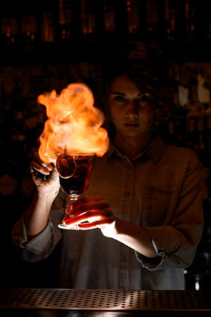 Woman at dark bar with wineglass of cocktail masterfully makes fire over it.