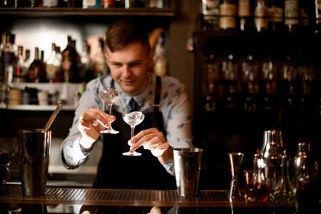 young bartender holds two glasses with ice in his hands 版權商用圖片