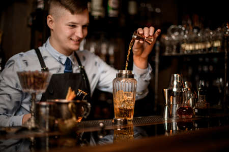 Young smiling bartender carefully pours drink to glassy shaker using beaker.