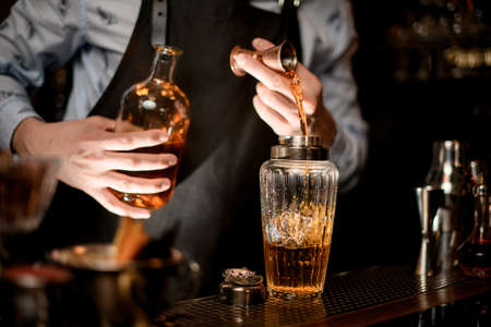 Close up. Barman carefully pours drink to glassy shaker using beaker. Archivio Fotografico