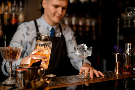 Young barman holds glassy cocktail shaker. Glass with ice stands on bar counter.