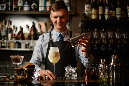 young smiling barman holds glass with ready-made cocktail