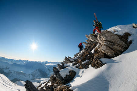 beautiful view of the snow-capped mountains. Two athletes with riding equipment on one of peaks. Foto de archivo