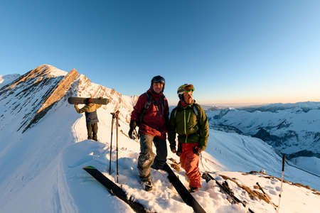 group of freeride snowboarders and skiers high in mountains