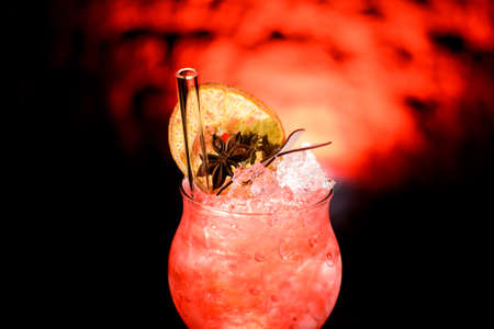 Close-up of illuminated glass of cold pink cocktail decorated with citrus, plant and glass tube to drink. Foto de archivo