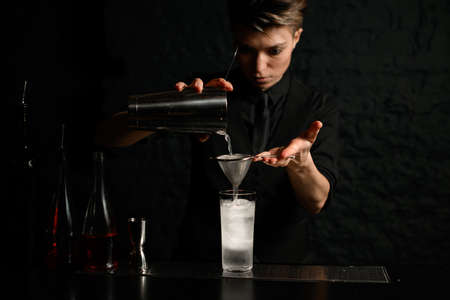 bartender in dark bar gently pours cocktail from steel shaker into glass