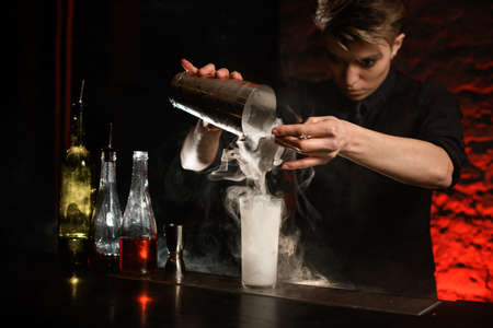 Professional bartender in dark bar gently pours cocktail from steel shaker into smoky glass with ice using sieve.