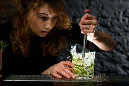 Woman bartender mixing cocktail and look at it.