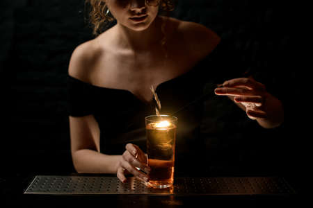 attractive girl at bar decorates glass with alcoholic drink by spikelet.