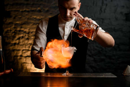 Close-up. Barman carefully pours cocktail to glass sprinkles to it and make fire. Reklamní fotografie
