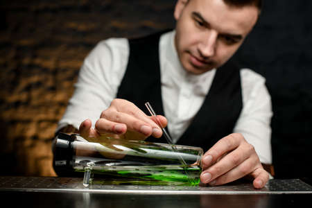 Man bartender inserts glassy tube in special designer glass flask Stock Photo