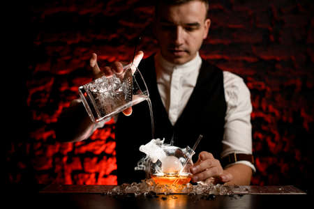 Man barman professionally pours cold drink into smoky designer flask