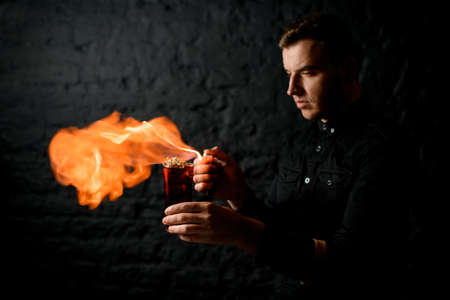 professional bartender holds his hands glass with cocktail and sets fire to it.