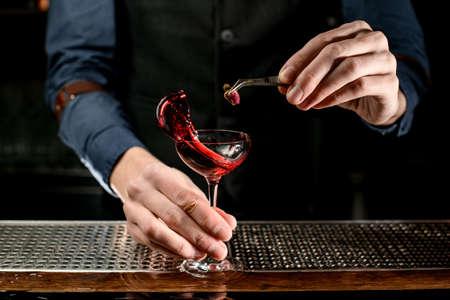 Male bartender decorates glass of splash wine by flower Banque d'images