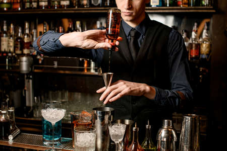 bartender holds in hand steel jigger and pours drink from bottle into it. Banque d'images