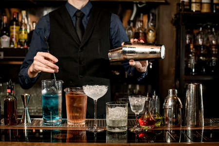 professional bartender holds steel shaker and mixes cocktail