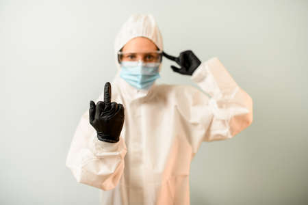 woman in protective clothes shows middle finger and points to head Reklamní fotografie