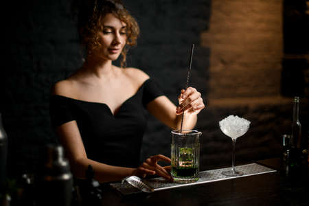 young handsome female barman gently stirring drink in cup with bar spoon