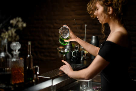 professional woman bartender in dark bar pours cocktail from cup to glass
