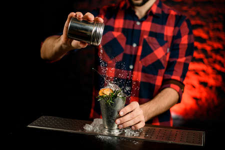 male bartender is holding metal jar and pouring powder on glass