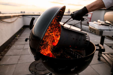 professional cook male with black gloves attentively pours burning coals into round black mobile barbecue grill.