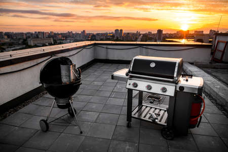 view of grill equipment which stands outdoor on roof of building. City and sunny sunset in background.