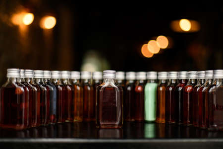 Front view on row of bottles with alcoholic drinks on bar counter.
