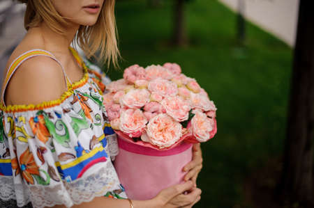 close-up. Girl in colorful dress carefully holds round box with fresh pink flowers Standard-Bild