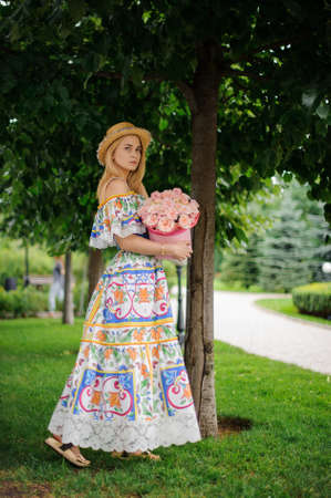 young woman in colorful dress and hat holds round decorative box with pink flowers.