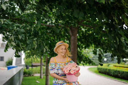 Cheerful smiling blonde girl with hat holds round box with pink flowers