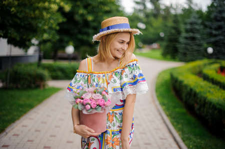 blonde woman with decorative box of flowers walks in the park and looks away Standard-Bild