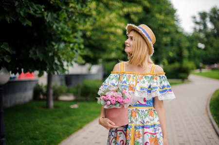 blonde woman with decorative box of flowers walks in the park