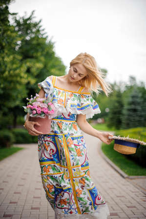 blonde girl in bright dress holds her hat and bouquet of flowers Standard-Bild