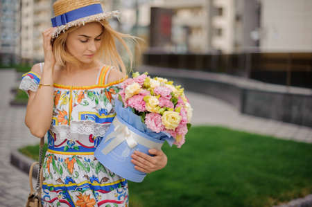 young blonde girl in straw hat holds decorative round box with flowers and looks at it.
