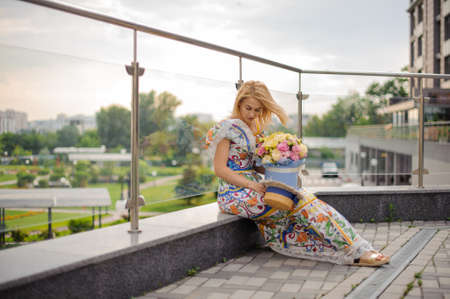Young beautiful girl holds round box of flowers and sits on the balcony.