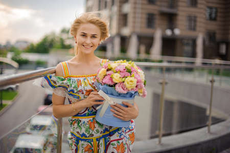 young attractive smiling woman blonde holds round box with flowers in her hand