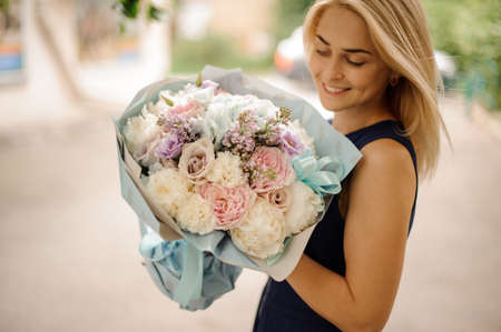 Young beautiful smiling blond woman holds bouquet in her hands and looks at it