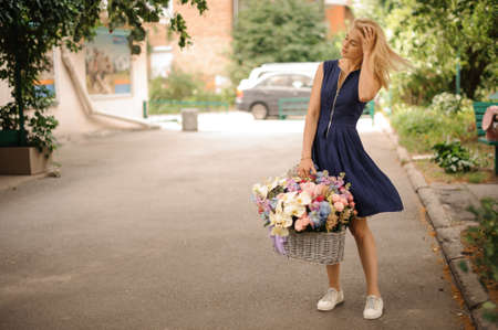 young girl in blue dress holds basket with flowers in one hand and straightens her hair with other hand