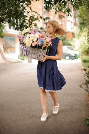 young girl walks with large basket with flowers. Standard-Bild
