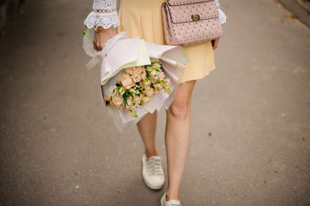 View of bouquet of roses in the hands of girl who walking in park