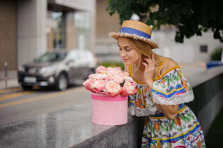 young girl in colorful dress and hat smelling fresh flowers Standard-Bild